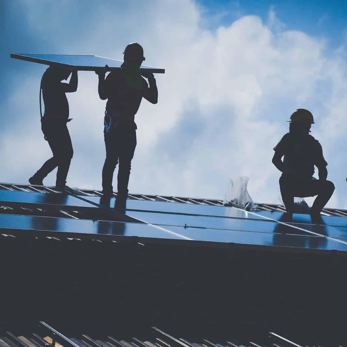 trabajadores colocando paneles solares para aires acondicionados